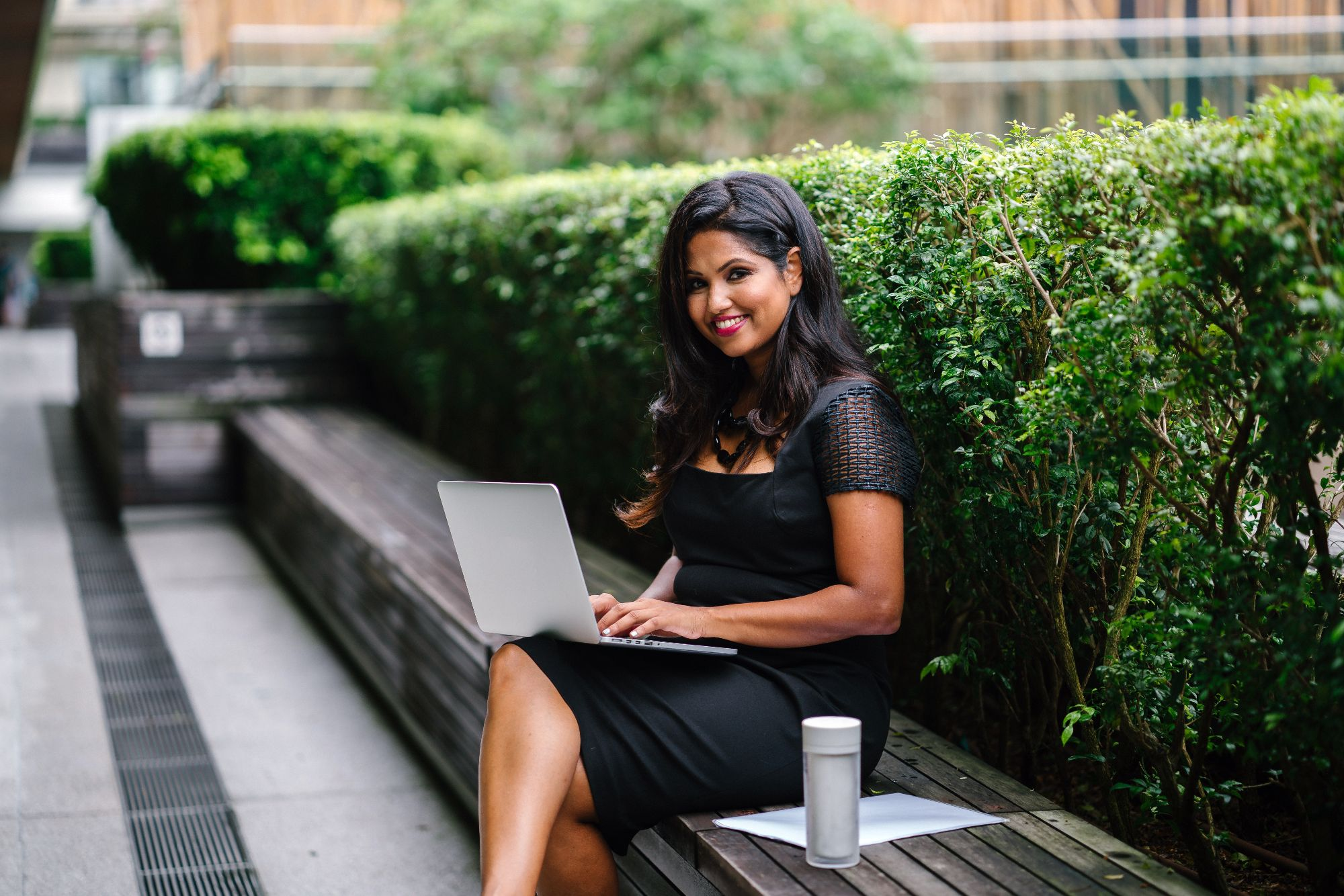 professional woman working on a laptop outside with coffee